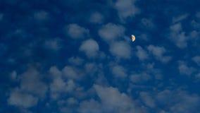 Mezza luna gialla nelle nuvole al crepuscolo Immagini Stock