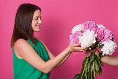 Mezza lunghezza sparata di signora, persona anonima per dare il suo grande bello mazzo dei fiori, essendo fotografando sullo stud immagine stock