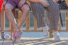 Mezza vista del corpo, fondo, giovane coppia che si siede su un banco di legno, lui che fuma una sigaretta immagini stock