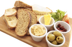 Mezze of artisan breads. Mezze of a variety of artisan breads on a wooden board, with green olives, sun dried tomatoes, hummus, and butter.The board is isolated Stock Images