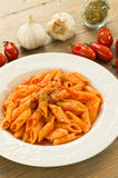 Mezze penne with tomato sauce and oregano. Dish of italian pasta cooked with tomato sauce, garlic and oregano, on the table wood Royalty Free Stock Image