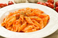 Mezze penne with tomato sauce and oregano. Dish of italian pasta cooked with tomato sauce, garlic and oregano, on the table wood Royalty Free Stock Photos