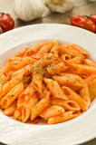Mezze penne with tomato sauce and oregano. Dish of italian pasta cooked with tomato sauce, garlic and oregano, on the table wood Stock Image