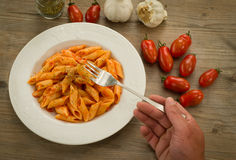 Mezze penne with tomato sauce and oregano. Dish of italian pasta cooked with tomato sauce, garlic and oregano, on the table wood Royalty Free Stock Photo