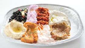 Mezzes side view. Side view of a restaurant take-away plate of Turkish or Arab mezzes, including hummus, sliced black olive salad, baba ganoush, onion, tomato Stock Image