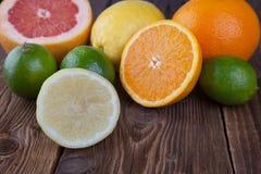 Mezzi agrume ed a metà arancio su legno Fotografia Stock