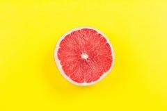 Mezzi agrumi del pompelmo su fondo giallo fotografia stock libera da diritti