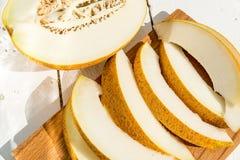 Mezzi melone e fette del melone sulla fine bianca del piatto Fotografia Stock Libera da Diritti