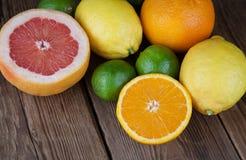 Mezzi pompelmo ed a metà arancio su legno Fotografie Stock Libere da Diritti