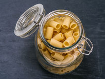 Mezzi Rigatoni pasta in a jar. Photo of Mezzi Rigatoni in an open jar on top of a slate background Royalty Free Stock Photos
