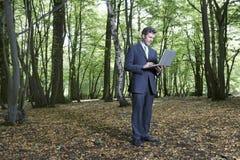 Mezzo di Using Laptop In dell'uomo d'affari della foresta fotografia stock libera da diritti