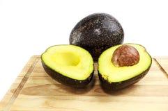 Mezzo e pieno dell'avocado sul piatto di legno Immagine Stock