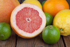 Mezzo pompelmo con altri frutti su legno Fotografie Stock