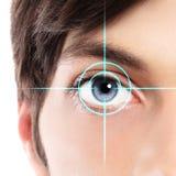 Mezzo primo piano del fronte dell'occhio azzurro da un hologra del laser e del giovane immagini stock