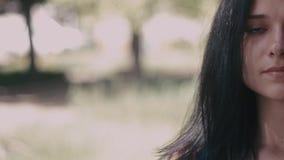 Mezzo ritratto del fronte della giovane donna castana esaminando la macchina fotografica e sorridendo sul fondo vago all'aperto video d archivio