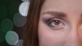 Mezzo ritratto del fronte del primo piano di giovane femmina attraente che esamina macchina fotografica con le luci del bokeh sui stock footage