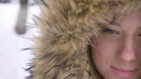Mezzo ritratto del primo piano di bella giovane ragazza caucasica in cappuccio della pelliccia che sorride grazioso nella macchin video d archivio