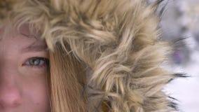 Mezzo ritratto del primo piano di giovane ragazza caucasica in cappuccio della pelliccia che guarda tranquillamente nella macchin archivi video
