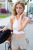 Mezzo ritratto di lunghezza di giovane donna affascinante dei capelli biondi che sta con la sua bicicletta classica nella via men fotografie stock libere da diritti
