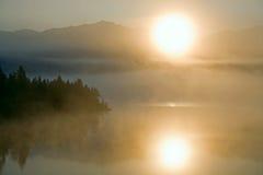 Mgła na halnym jeziorze i powstającym słońcu Zdjęcia Stock
