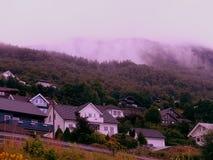 Mgła nad górską wioską z Klasyczną Skandynawską architekturą obraz stock