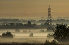 Mgła nad polami i wierza linie energetyczne na obrzeżach miasto Obraz Royalty Free
