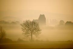 Mgławy zima ranek z krajobrazem i kościół fotografia stock