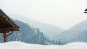 Mgłowa wieś w śnieżnej dolinie Wzgórza i góry z sosny ans świerkowym lasem zakrywającym z śniegiem ablegrujący