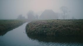 Mgłowy holendera gospodarstwo rolne na zieleni i mokry łąka krajobraz w zimie Z płochą w przedpolu zbiory