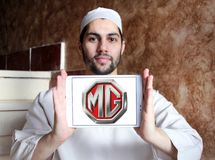MG Motor company logo. Logo of MG Motor company on samsung tablet holded by arab muslim man. MG Motor UK Limited MG Motor is an automotive company headquartered Stock Image