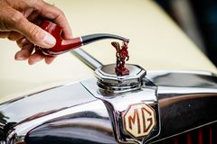 MG Pegasus. A man tapping his MG`s pegasus hood ornament with his pipe Royalty Free Stock Images