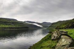 Mgły lying on the beach na górach, Faroe wyspy, Dani, Europa Zdjęcia Stock