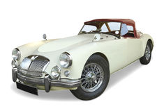 MGA Roadster classic sports car. White MGA (Morris Garages) 1950's Roaster classic sports car with wire wheels, head and fog lights, soft top and luggage rack Royalty Free Stock Image