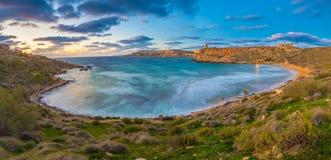 Mgarr,马耳他-著名Ghajn Tuffieha海湾的全景地平线视图在蓝色小时 免版税库存照片
