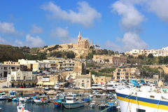 Mgarr, Gozo, Republic of Malta. With its port and the church on the hill Stock Photos