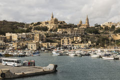 Mgarr Harbour on Gozo, Malta. Entrance to Mgarr Harbour on Gozo, Malta with two churches on skyline Royalty Free Stock Image