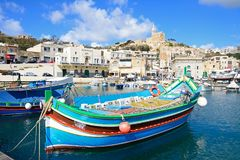Mgarr harbour and town, Gozo. Traditional fishing boats in the harbour with the Our Lady of Lourdes church on the hillside to the rear, Mgarr, Gozo, Malta Royalty Free Stock Photo