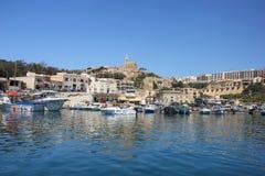 Mgarr Malta - Maj 2018: Sikt Mgarr för Gozo färjaterminal Fjärd med yachter på förgrund och gammal stad med kyrkan på överkanten  fotografering för bildbyråer