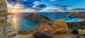 Mgarr, Malta - Panorama of Gnejna bay and Golden Bay, the two most beautiful beaches in Malta. At sunset with beautiful colorful sky and golden rocks taken from Royalty Free Stock Photo