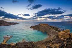Mgarr, Malta - Panorama of Gnejna bay, the most beautiful beach in Malta at sunset. With beautiful colorful sky and golden rocks taken from Ta Lippija Royalty Free Stock Images