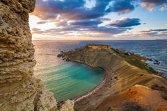 Mgarr, Malta - Panorama of Gnejna bay, the most beautiful beach in Malta at sunset. With beautiful colorful sky and golden rocks taken from Ta Lippija Stock Photos