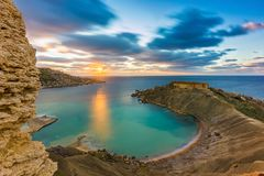 Mgarr, Malta - Panorama of Gnejna bay, the most beautiful beach in Malta at sunset with beautiful colorful sky. And golden rocks taken from Ta Lippija Stock Photos