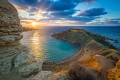 Mgarr, Malta - Panorama of Gnejna bay, the most beautiful beach in Malta at sunset. With beautiful colorful sky and golden rocks taken from Ta Lippija Royalty Free Stock Photo