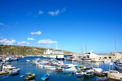 Mgarr Port and marina, Gozo. Colourful fishing boat moored in the harbour with the Gozo ferry moored in the port to the rear, Mgarr, Gozo, Malta, Europe Royalty Free Stock Photos