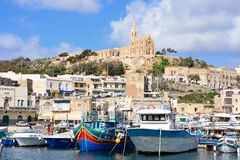 Mgarr town and harbour, Gozo. Traditional fishing boats in the harbour with the Our Lady of Lourdes church on the hillside to the rear, Mgarr, Gozo, Malta Royalty Free Stock Image