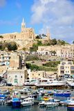 Mgarr town and harbour, Gozo. View of boats in the harbour with the Ghajnsielem Parish church and Our lady of Lourdes church to the rear, Mgarr, Gozo, Malta Royalty Free Stock Images