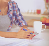Mgazine чтения молодой женщины в кухне дома Стоковое фото RF
