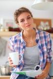 Mgazine de lecture de femme dans la cuisine à la maison Photo libre de droits