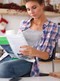 Mgazine de lecture de femme dans la cuisine à la maison Images stock