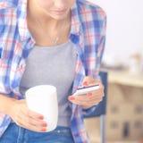 Mgazine de lecture de jeune femme dans la cuisine à la maison Images stock